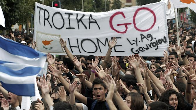 Cypriot students shout slogans near the presidential palace in capital Nicosia, on Tuesday, March 26, 2013. Banks across Cyprus remain firmly padlocked Tuesday after financial authorities extended the country's bank closure, fearing worried depositors will rush to drain their accounts. The shut-down is hammering businesses, which have been without access to their funds for more than a week.(AP Photo/Petros Giannakouris)