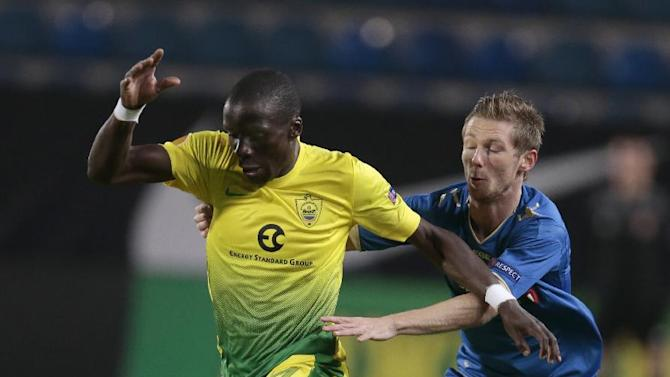 Anzhi's Benoit Angbwa, left, runs away from Tromso's Thomas Drage as they struggle for the ball during the Europa League group K soccer match between Anzhi Makhachkala and Tromso IL at Saturn stadium in Ramenskoye, outside Moscow, in Russia, on Thursday, Oct. 24, 2013