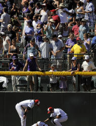 Colorado Rockies Charlie Blackmon, left, and Ryan Spilborghs, right, check on the condition of Carlos Gonzalez, center, who ran into the wall on a fly ball, in the seventh inning of an interleague baseball game against the Kansas City Royals in Denver on Sunday, July 3, 2011. Gonzalez was down on the warning track for several minutes before being taken off the field on a cart. The Royals won 16-8. (AP Photo/Chris Schneider)