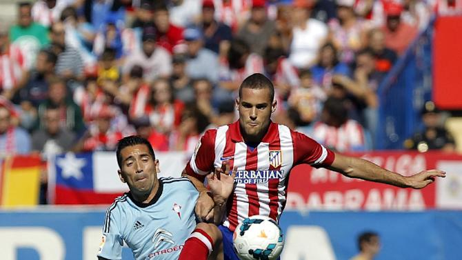 Atletico de Madrid's Mario Suarez, right, in action with Celta de Vigo's Charles from Brazil, left, during a Spanish La Liga soccer match at the Vicente Calderon stadium in Madrid, Spain, Sunday, Oct. 6, 2013