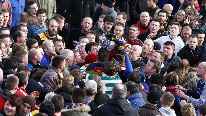 The ball breaks from the hug during the annual Shrovetide football match in Ashbourne