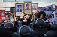"Protesters hold up pictures of some of those killed during a crackdown on anti-government rallies two years ago as former Thai prime minister Abhisit Vejjajiva (not pictured) appears at a justice ministry building to be charged with murder over a civilians' death, in Bangkok on December 13, 2012. Terrorism trial against Thai leaders of the 2010 ""Red Shirt"" protests began on Friday"