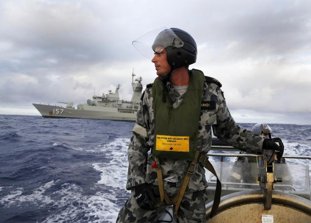 Standing in a rigid hull inflatable boat launched from HMAS Perth, Leading Seaman, Boatswain's Mate, William Sharkey searches for possible debris in the southern Indian Ocean during the continuing