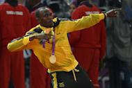 "Jamaica's Usain Bolt poses on the podium with his gold medal after Jamaica won and set a new world record in the men's 4X100 relay final at the athletics event of the London 2012 Olympic Games in August. Bolt vowed Monday to defend his Olympic sprint titles in Rio but, buoyed by the West Indies' World Twenty20 triumph, declared that cricket was his ""first love"""
