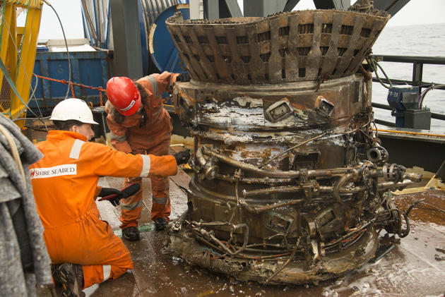 In this image provided by Bezos Expeditions, workers inspect a thrust chamber of an Apollo F-1 engine recovered from the bottom of the Atlantic Ocean in March 2013. An expedition led by Amazon CEO Jef