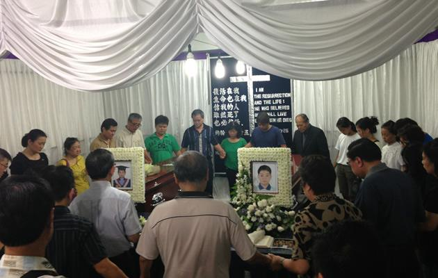Family and friends pray over the coffins of brothers Nigel and Donovan Yap