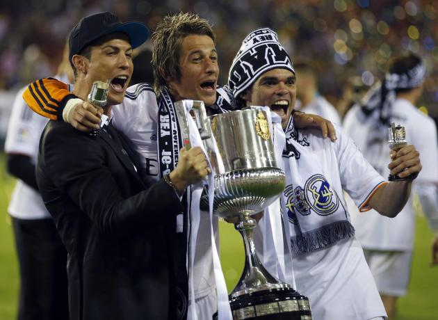 Real Madrid's Ronaldo, Coentrao and Pepe celebrate with the trophy after winning the King's Cup final soccer match against Barcelona at Mestalla stadium in Valencia