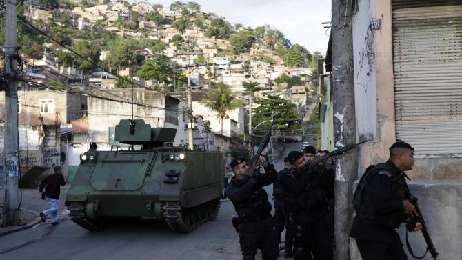 Police officers take up position next to a Brazilian Navy combat car at the Arvore Seca slum in the Lins slum complex during an operation in Rio de Janeiro