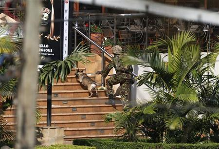 A Kenyan soldier holding a dog by its leash enters the main gate of Westgate Shopping Centre in Nairobi September 22, 2013. REUTERS/Goran Tomasevic