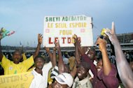 "Togolese supporters hold a placard reading ""Shevi Adebayor, Togo's only hope"" as they celebrate at the end of the Africa Cup of Nations qualifier on October 14, 2012 in Lome. Togo beat Gabon 2-1 to qualify for the 2013 showpiece in South Africa"