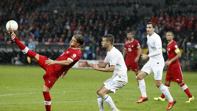 Switzerland's Michael Lang, left, fights for the ball with Slovenia's Andraz Struna during the FIFA World Cup 2014 group E qualifying soccer match between Switzerland and Slovenia at the Stade de Suisse stadium in Bern, Switzerland, Tuesday, October 15, 2013