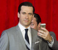 FILE - This May 9, 2014, file photo, shows actor Jon Hamm, right, taking a selfie at the unveiling of his wax figure at Madame Tussauds in New York. Selfie is one of the 150 new words appearing in Merriam-Webster's Collegiate Dictionary and the company's free online database. (Photo by Charles Sykes/Invision/AP, File)