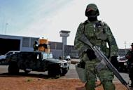 Mexican soldier stand guard outside the Piedras Negras federal prison where a group of prisoners escaped on September 18, 2012. The Mexican authorities are hunting for the 131 escaped inmates near the US border
