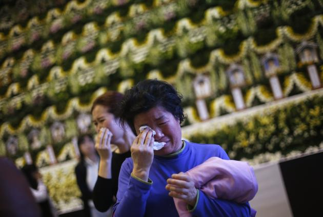 Mourners cry after paying tribute in Ansan, at temporary group memorial altar for victims of capsized passenger ship Sewol