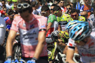 """Cyclists observe a minute of silence to honor Wouter Weylandt, prior to the start of the fourth stage of the Giro d'Italia, Tour of Italy cycling race, in Genoa, Italy, Tuesday, May 10, 2011. The Leopard-Trek team will continue to ride in the Giro d'Italia despite the death of cyclist Wouter Weylandt. The 26-year-old Belgian crashed Monday during a descent after clipping a wall during the third stage of the race and died at the scene despite medical staff trying to revive him for 40 minutes. """"We will start out of respect for the family of Weylandt and also to share our grief with the world of cycling,"""" Leopard Trek general manager Brian Nygaard said Tuesday."""