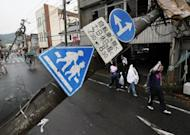 People walk past a collapsed electric pole after a tornado swept through a residential area of Tsukuba city in Ibaraki prefecture, north east of Tokyo. The tornado killed a teenager, destroyed dozens of homes and cut power to around 20,000 households