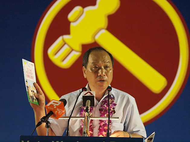 "WP chief Low Thia Khiang holds up another copy of the PAP manifesto that was distributed to Hougang residents, saying, ""I've told the PAP it's not their money — it is the country's money, and Lee Kuan Yew admitted before that the government's money is the people's money,"" (Yahoo! photo/Jason Ong)"