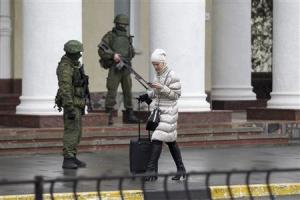 A woman walks past armed men at the Simferopol airport…