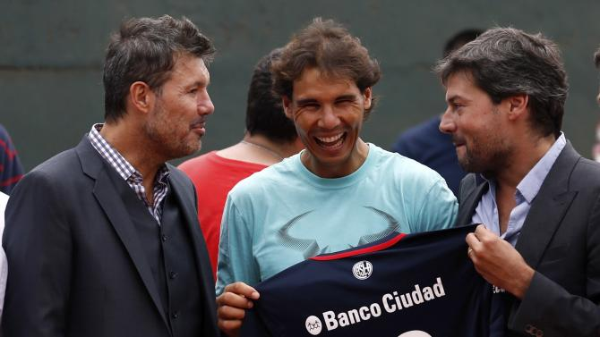Spain's tennis player Rafael Nadal laughs next to Matias Lammens, president of soccer club San Lorenzo de Almagro and San Lorenzo's vice-president Marcelo Tinelli as they give him a soccer jersey