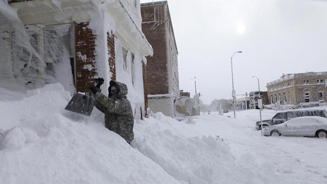 Chad Hoffman clears snow from the entrance to his apartment building in Rapid City, S.D,, Saturday, Oct. 5, 2013. South Dakota emergency agencies are asking snowmobile operators in the Rapid City area to help find motorists stranded by an autumn storm. The National Weather Service says the storm dumped at least three and a half feet of wet, heavy snow in the Black Hills. Rapid City had 21 inches, but 31 inches was recorded just a mile southwest of the city. (AP Photo/Rapid City Journal, Chris Huber)