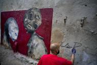 In this Feb. 9, 2017 photo, the urban artist Yulier Rodriguez Perez, 27, artistically known as Yulier P. puts his signature on a painting after finishing it on a street in Old Havana, Cuba. (AP Photo/Ramon Espinosa)