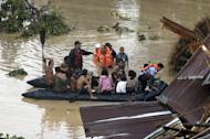 Police rescue trapped residents following a flash flood that inundated Cagayan de Oro city, Philippines, Saturday, Dec. 17, 2011. A tropical storm triggered flash floods in the southern Philippines, killing scores of people and missing more. Mayor Lawrence Cruz of nearby Iligan said the coast guard and other rescuers were scouring the waters off his coastal city for survivors or bodies that may have been swept to the sea by a swollen river. (AP Photo/Froilan Gallardo)