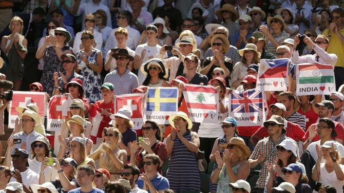 Fans of Roger Federer of Switzerland hold up flags during his match against Damir Dzumhur of Bosnia and Herzegovina at the Wimbledon Tennis Championships in London