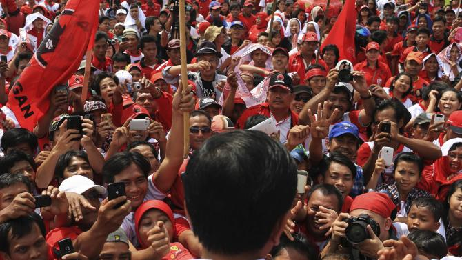 Supporters greet Jakarta governor and presidential candidate Widodo during a campaign in Jakarta