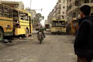 An opposition fighter crosses an area under attack by snipers from the government forces on his motorcycle in the front line of the Bustan al-Basha district of Aleppo on January 2, 2012