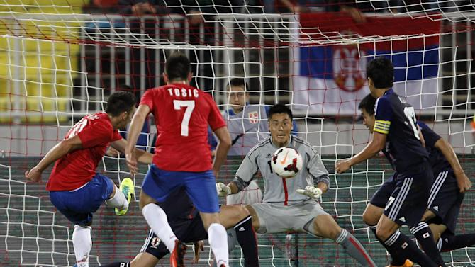 Serbia's Dusan Tadic, left, scores during an international friendly against Japan at Karadjordje stadium in Novi Sad, Serbia, Friday, Oct. 11, 2013
