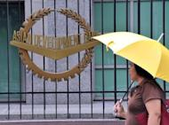 A pedestrian walks past a logo of Asian Development Bank (ADB) displayed outside its headquarters in Manila, 2010. China's yuan is increasingly being used to settle trade transactions in Asia, gradually cementing its way to becoming a regional 'anchor' currency, the Asian Development Bank (ADB) said