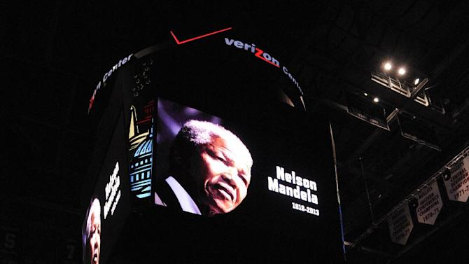 An image of the late Nelson Mandela is displayed on the scoreboard before an NBA basketball game between the Washington Wizards and the Milwaukee Bucks, Friday, Dec. 6, 2013, in Washington