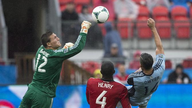 Toronto FC 's goalkeeper Joseph Bendik (12) punches the ball clear from Sporting Kansas City's Dom Dwyer during the second half of an MLS soccer game in Toronto on Saturday, Sept, 21, 2013