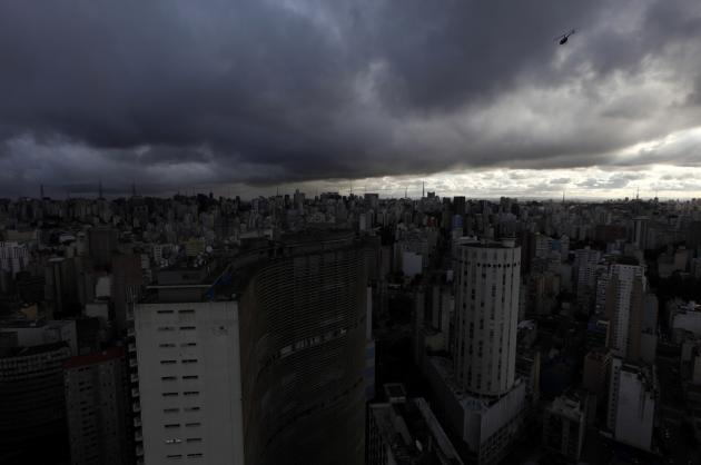 An helicopter (R) flies over the sky of the city of Sao Paulo