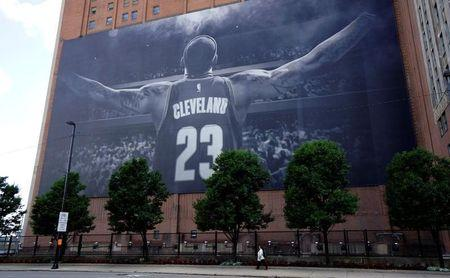 A woman on the sidewalk is dwarfed by a giant picture of NBA basketball Cleveland Cavaliers player LeBron James in downtown Cleveland across the street from the Republican National Convention