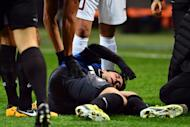 Inter Milan's Argentinian forward Diego Milito reacts in pain after being injured during the UEFA Europe League football match between Inter Milan and CFR Cluj at San Siro Stadium in Milan on February 14, 2013. Milito is out for the season after suffering a cruciate ligament injury to his left knee