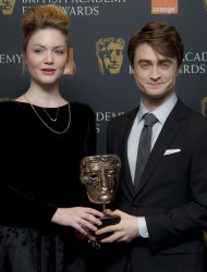 British actors Daniel Radcliffe and Holliday Grainger hold a Bafta Award after they announced the British Academy Film Award nominations in Piccadilly, London, Tuesday, Jan. 17, 2012. (AP Photo/Joel Ryan)