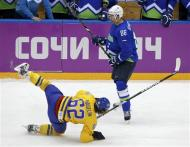 Slovenia's Sabahudin Kovacevic (R) hits Sweden's Carl Hagelin during the second period of their men's quarter-finals ice hockey game at the 2014 Sochi Winter Olympic Games, February 19, 2014. REUTERS/Grigory Dukor