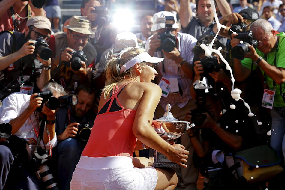 Sharapova of Russia poses for photographers as she holds her trophy after winning the final match over Suarez Navarro of Spain at the Rome Open tennis tournament in Rome