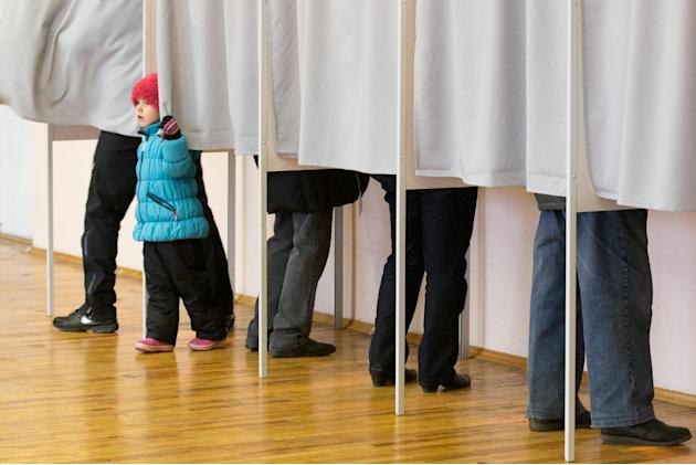 A little girl looks out of a voting booth at a polling station in Tallinn, Estonia, on Sunday, March 1, 2015. Estonians are voting for a new Parliament in an election dominated by economic issues and