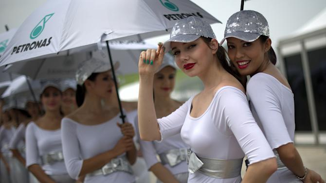Grid girls pose for the pictures in the paddock area during the qualifying session of Formula One's Malaysian Grand Prix at the Sepang International Circuit in Sepang on March 24, 2012. AFP PHOTO / Saeed KHAN (Photo credit should read SAEED KHAN/AFP/Getty Images)