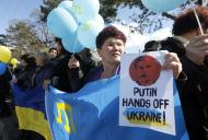 "Participants hold placards and shout slogans during an anti-war rally in the Crimean town of Bakhchisaray March 5, 2014. Russia said on Wednesday it could not order ""self-defence"" forces in Crimea back to their bases ahead of the first face-to-face talks with the United States on easing tensions over Ukraine and averting the risk of war. REUTERS/Vasily Fedosenko (UKRAINE - Tags: POLITICS CIVIL UNREST)"