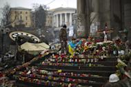 An anti-Yanukovych protester stands at a memorial for the people killed in clashes with the police at Kiev's Independence Square, the epicenter of the country's current unrest, Saturday, March 1, 2014. The pro-Russian prime minister of Ukraine's restive Crimea is claiming control of all military forces, police and other security services in the region. In a statement reported by local and Russian news agencies on Saturday, Sergei Aksenov declares that the armed forces, the police, the national security service and border guards will answer only to his orders. He says that any commanders who don't agree should leave their posts. (AP Photo/Emilio Morenatti)