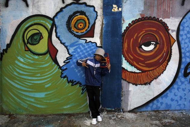 "A boy poses between graffiti-filled walls along ""Beco do Batman"" (Batman's alley) in the Vila Madalena neighbourhood, which is a well-known open-air graffiti museum, in Sao Paulo"
