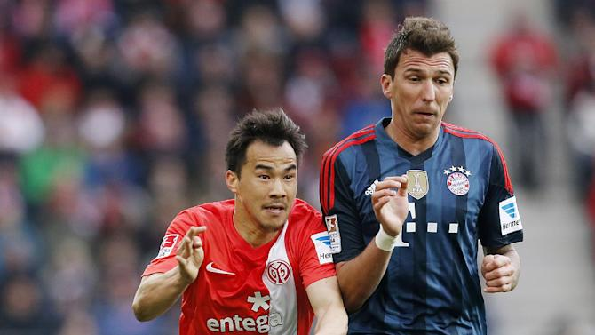 Mainz's Shinji Okazaki of Japan, left, and Bayern's Mario Mandzukic of Croatia challenge for the ball during a match of German first soccer division,  Bundesliga, between FSV Mainz 05 and Bayern Munich in Mainz, Germany, Saturday, March 22, 2014