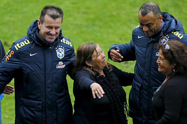 Brazil's head coach Dunga and his assistant Cafu pose with victims of an earthquake after a team training session at Santiago