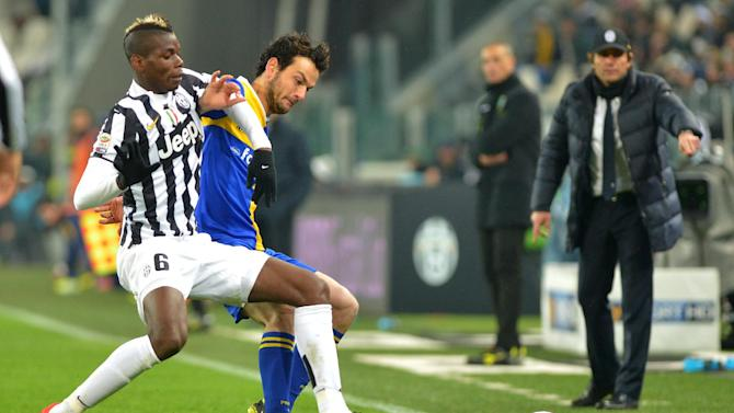 Juventus midfielder Paul Pogba, of France, left, challenges the ball with Parma' midfielder Marco Parolo during a Serie A soccer match between Juventus and Parma at the Juventus stadium, in Turin, Italy, Wednesday, March 26, 2014