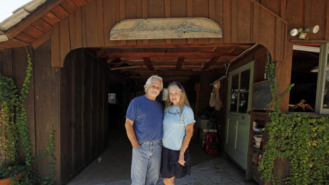 "In this Thursday, Sept. 18, 2012 photo, Tony Dow, actor, director and artist, and his wife Lauren pose at their home and studio in the Topanga area of Los Angeles. When it comes time to sitting down in a studio and carving out bronze and wooden sculptures inspired by the nature all around him, Wally isn't leaving it up to the Beav these days. Dow, who famously played the Beaver's older brother Wally on the classic 1950s-60s sitcom ""Leave it To Beaver,"" is carving out a name for himself in the art world these days, as an abstract artist. (AP Photo/Reed Saxon)"
