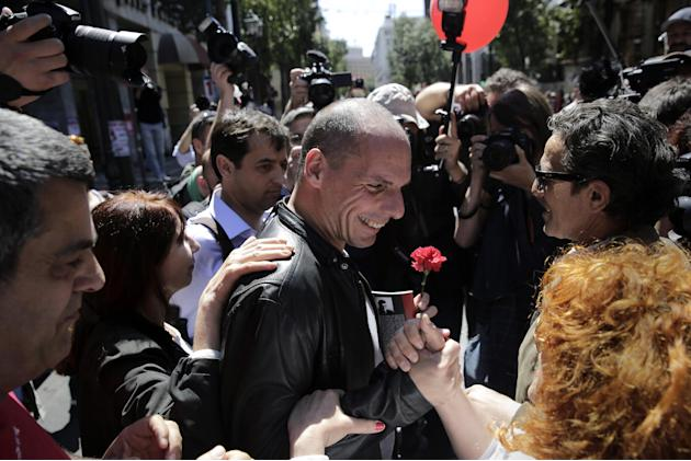 A protester greets Greek Finance Minister Yanis Varoufakis, center, during a May Day protest in central Athens, Friday, May 1, 2015. In financially struggling Greece, an estimated 13,000 people took p