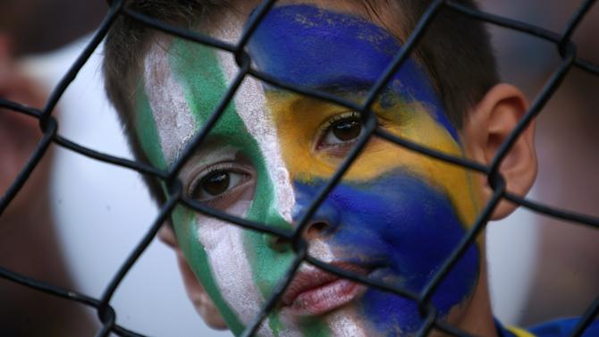 A Boca Juniors' fan wears face paint with the colours of Brazilian soccer team Chapecoense during a match to pay tribute to the victims of the plane crash in Colombia in Buenos Aires